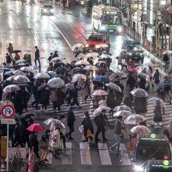 La gente cruza una calle en el área de Shibuya durante una lluvia en Tokio cuando los funcionarios extendieron el estado de emergencia por el coronavirus Covid-19 por quince días. | Foto:AFP