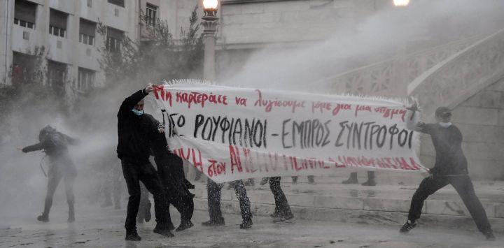 Los manifestantes intentan sostener una pancarta bajo el agua rociada por la policía antidisturbios en el centro de Atenas.
