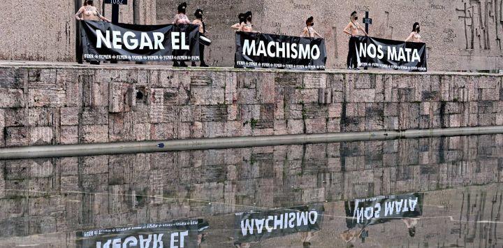 Activistas de Femen sostienen pancartas, junto con una cruz con el número 1082 en referencia al número de femicidios desde que comenzó el rastreo en España en 1999 durante una protesta en la Plaza de Colón de Madrid.
