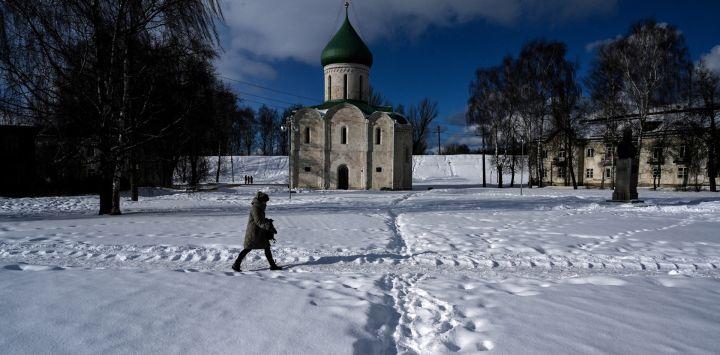 Una mujer camina frente a la catedral del siglo XII en el centro histórico de la ciudad de Pereslavl-Zalessky, es parte del llamado Anillo de Oro de Rusia, que comprende varias ciudades fuera de Moscú.