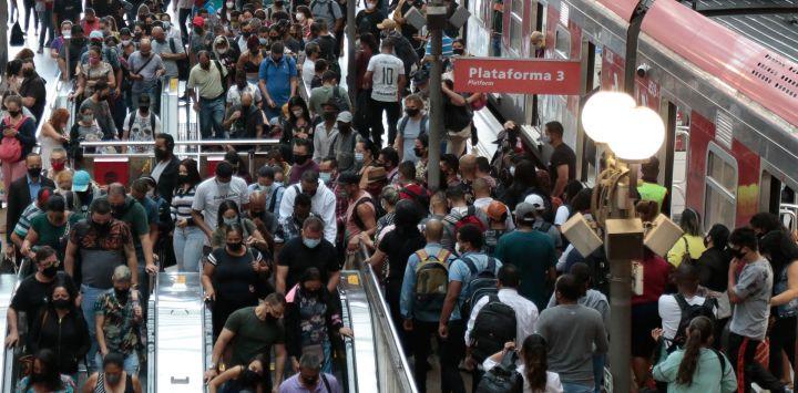 """Decenas de pasajeros caminan después de desembarcar del tren en la estación de Luz en el centro de Sao Paulo, Brasil, en medio de la pandemia. El estado más grande de Brasil, Sao Paulo, declaró el miércoles nuevas restricciones de """"código rojo"""" sobre COVID-19."""
