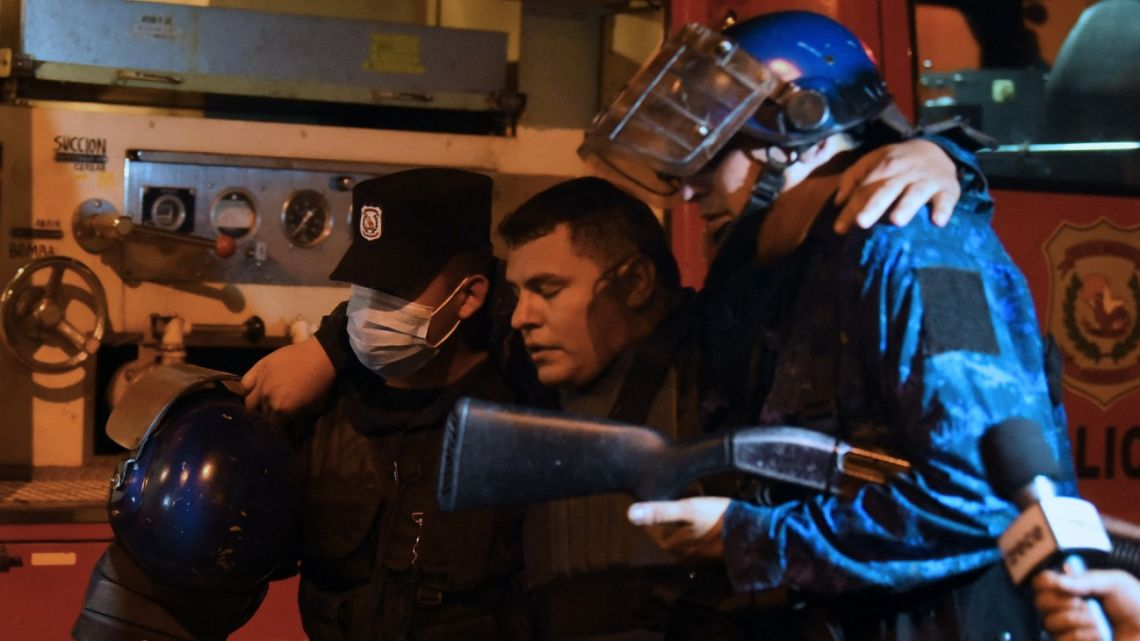 An injured policeman is helped by colleagues during confrontations with demonstrators following a protest against corruption and lacks in the health system, demanding the resignation of Paraguayan President Mario Abdo Benítez, in Asunción, on March 5, 2021.