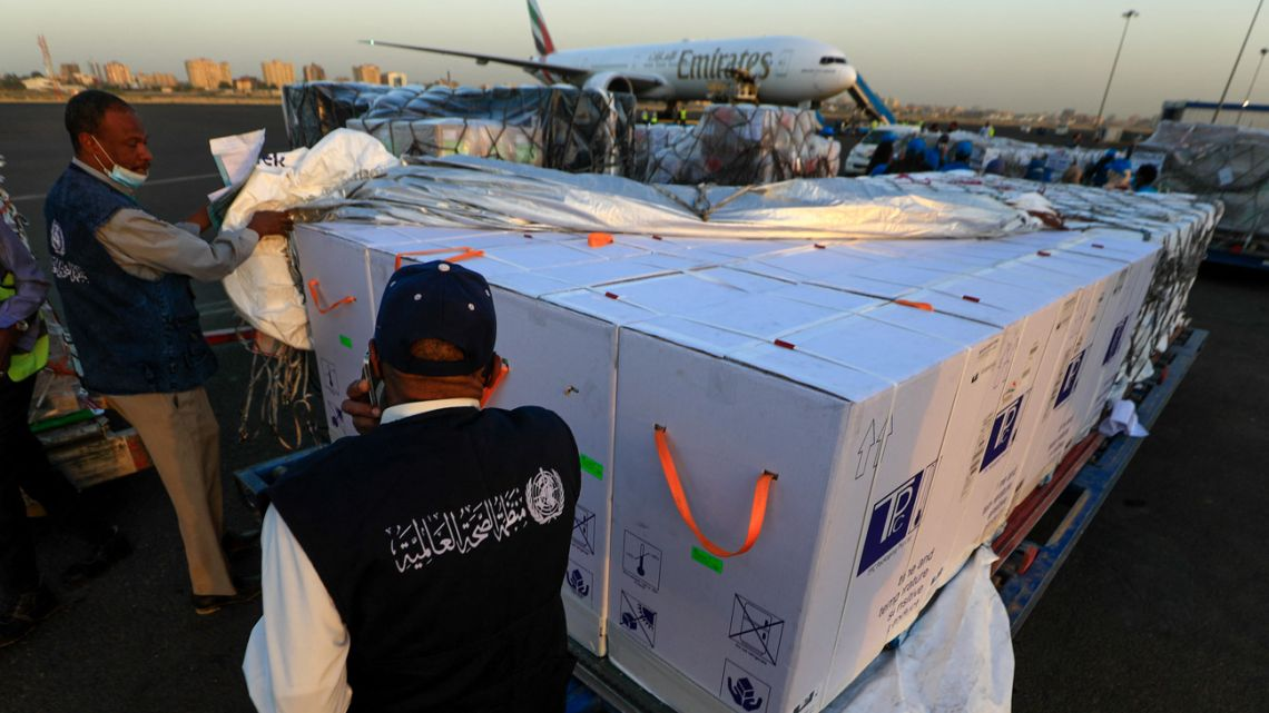 An employee of the World Health Organisation (WHO) supervises the arrival of the first batch of coronavirus vaccines, at Khartoum airport in the Sudanese capital, on March 3, 2121.