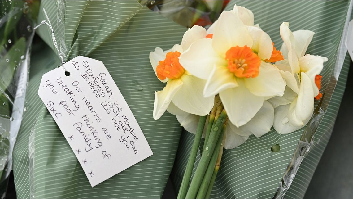 Flowers and a message of condolence for Sarah Everard are seen at the woodland where police officers found human remains near Ashford, southeast England, on March 12, 2021.