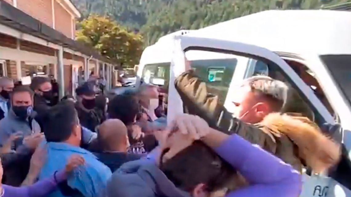 Protesters crowd President Alberto Fernández as he attempts to get on a vehicle in Lago Puelo, Chubut Province.