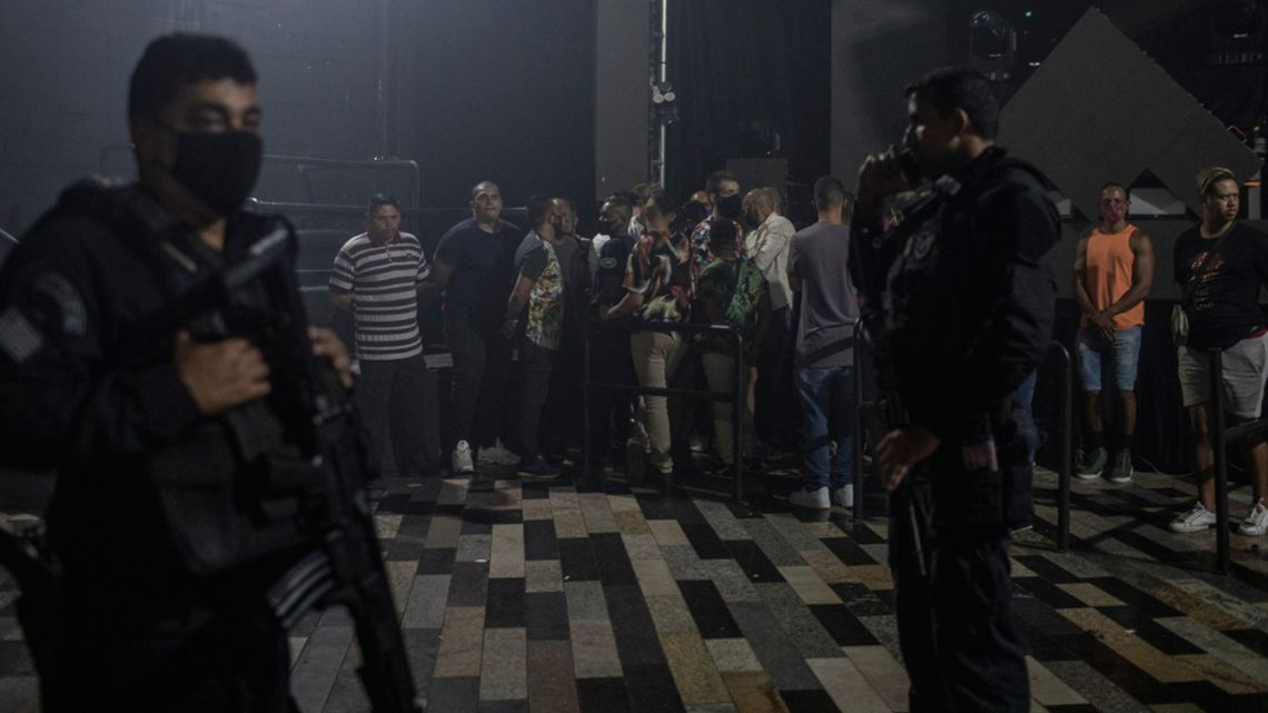 Health officials and police officers inspect a business open after lockdown restrictions in São Paulo, Brazil, on Saturday, March 6, 2021.