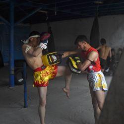 Esta foto muestra a los atletas reflejados en un espejo mientras entrenan en forma de artes marciales Muay Thai en un club en la provincia de Bamiyán. | Foto:Wakil Kohsar / AFP