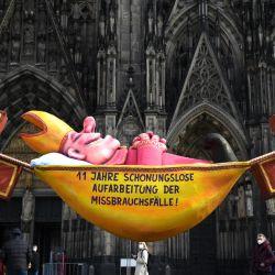 Una escultura del artista Jacques Tilly con el lema '¡11 años de investigación incesante de los casos de abuso!' se ve frente a la Catedral de Colonia en Colonia, Alemania occidental, cuando se publicó un informe largamente esperado sobre la violencia sexual presuntamente cometida por clérigos y laicos en la principal diócesis de Alemania. | Foto:Ina Fassbender / AFP