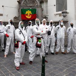 Personas vestidas con trajes protectores blancos se reúnen frente a la estatua del Manneken Pis. | Foto:Hatim Kaghat / varias fuentes / AFP