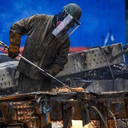 Un empleado trabaja en el desmantelamiento de un autobús en el depósito de chatarra del transporte público  | Foto:Juan Barreto / AFP