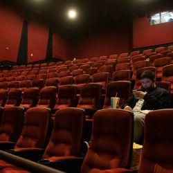 Un espectador se sienta a esperar que comience su película en el teatro AMC Burbank el día de la reapertura en Burbank, California. - Los Ángeles y el sur de California pueden reabrir parcialmente las salas de comedor y cine bajo techo, anunció el gobernador Gavin Newsom la semana pasada ya que la región alcanzó criterios clave de salud. | Foto:Valerie Macon / AFP