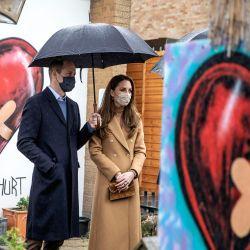 El príncipe William, duque de Cambridge (izq.) De Gran Bretaña y la duquesa de Cambridge, Catherine, duquesa de Cambridge, ambos con cubiertas faciales debido al Covid-19, conversan con miembros del servicio de ambulancia en el jardín del bienestar durante una visita a la estación de ambulancias de Newham en el este de Londres. | Foto:Richard Pohle / POOL / AFP