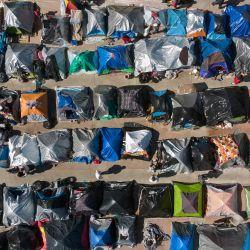 Vista aérea de un campamento de migrantes donde los solicitantes de asilo esperan a que las autoridades estadounidenses les permitan iniciar su proceso migratorio fuera del puerto de cruce de El Chaparral en Tijuana, estado de Baja California, México. | Foto:Guillermo Arias / AFP