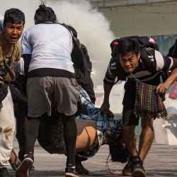 Los manifestantes llevan a un hombre herido baleado con balas reales por las fuerzas de seguridad durante la represión de las manifestaciones contra el golpe militar en Yangon. | Foto:STR / AFP