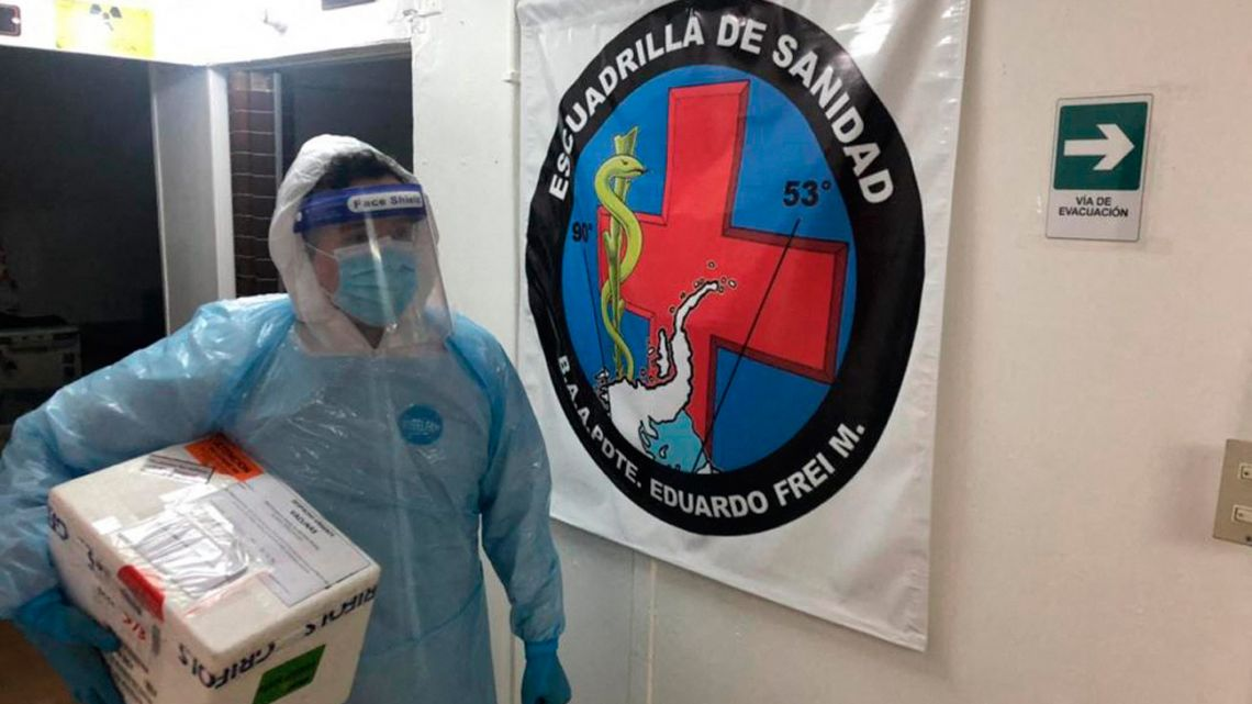 Handout picture released by the Chilean Air Force showing a health worker carrying a cooler containing doses of Sinovac's CoronaVac coronavirus vaccine at a Chilean Air Force base in Antarctica, Chile March 14, 2021.