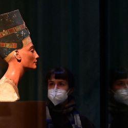 Un visitante con una mascarilla mira el Busto de la Reina Nefertiti de Tell el-Amarna, la exposición más famosa del Neues Museum con su colección de arte egipcio, en Berlín, ya que era posible visitar algunos museos estatales. nuevamente en medio de la nueva pandemia de coronavirus / COVID-19. | Foto:Tobias Schwarz / AFP