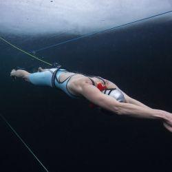 La apneista finlandesa de 45 años Johanna Nordblad entrena dos días antes de establecer el primer récord mundial oficial CMAS de buceo libre bajo hielo sin traje de buceo (solo un traje de baño), para realizar 103 m bajo hielo de 60 cm de espesor, en 2'42 Mn sin briething. | Foto:Elina Manninen / AFP