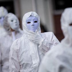 Manifestantes vestidos con trajes de protección blancos y máscaras participan en una manifestación contra un proyecto de ley de  | Foto:Loic Venance / AFP