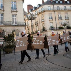Los trabajadores del sector cultural que ocupan el Teatro Graslin de Nantes realizan una cuenta atrás del toque de queda en Nantes, en el oeste de Francia, durante una manifestación para exigir la reapertura de lugares y espacios culturales, un año después de sus primeros cierres como parte de las medidas destinadas a frenar la propagación de la pandemia de Covid-19. | Foto:Loic Venance / AFP