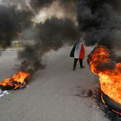 Un manifestante envuelto en la bandera nacional iraquí pasa junto a neumáticos en llamas durante los enfrentamientos entre manifestantes antigubernamentales en la ciudad santuario central de Nayaf, en Irak. | Foto:Ali Najafi / AFP