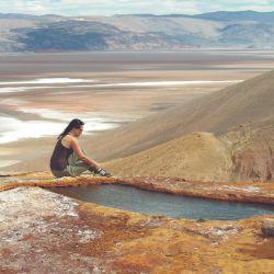 Dos viajeros se toman fotos junto a la poza termal de Vega Botijuela, a más de 4.000 msnm.