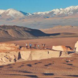 Momento de relax, un grupo de turistas saluda a la cámara lejana para tomarse una foto trepados a una de las formaciones del Campo de Piedra Pómez (Catamarca).