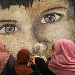 Mujeres palestinas participan en una protesta contra los recortes en la distribución de ayuda alimentaria, frente a la sede de la Agencia de Obras Públicas y Socorro de las Naciones Unidas (OOPS) en la ciudad de Gaza.   Foto:Mohammed Abed / AFP