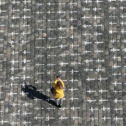 Una mujer toma una foto en la Plaza de la Ciudad Vieja de Praga, donde se han dibujado miles de cruces en el pavimento para conmemorar el primer aniversario desde la muerte del primer paciente con coronavirus checo.   Foto:Michal Cizek / AFP