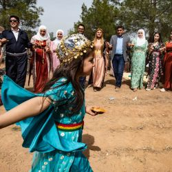 Una niña vestida con ropas tradicionales baila durante una celebración kurda siria en el segundo día de Nowruz, el Año Nuevo persa, en el campo de la ciudad de Qahtaniyah en la provincia de Hasakah, al noreste de Siria, cerca de la frontera con Turquía.   Foto:Delil Souleiman / AFP