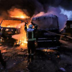 Los miembros de la defensa civil siria intentan apagar el incendio de varios camiones y vehículos de carga después de los ataques aéreos en un depósito cerca del cruce fronterizo de Bab al-Hawa entre Siria y Turquía en la provincia de Idlib, al noroeste de Siria, controlada por los rebeldes.   Foto:Abdulaziz Ketaz / AFP