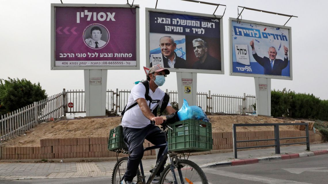 """A man cycles across a street near electoral billboards of the Israeli Likud party showing (R to L) its leader Benjamin Netanyahu giving two thumbs up with text in Hebrew reading """"returning to smile""""; and another showing Netanyahu next to his opponent Yair Lapid with text reading """"next Prime Minister: Lapid or Netanyahu"""", in the southern Israeli city of Beersheba on March 22, 2021, a day ahead of the fourth national election in two years."""
