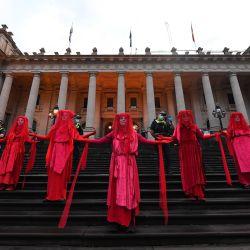 Los manifestantes son vistos durante una protesta de Rebelión de extinción frente al Parlamento Estatal de Victoria en Melbourne. El grupo activista Extinction Rebellion está llevando a cabo una serie de eventos en las capitales australianas, fomentando la acción sobre cuestiones climáticas y ambientales. | Foto:AAP / James Ross / DPA