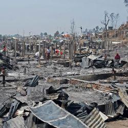 En la foto se ven personas en medio de los escombros en un campo de refugiados rohingya en Ukhia después de que un gran incendio obligó a unas 50.000 personas a huir. | Foto:AFP