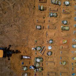 Vista aérea que muestra un tractor cavando fosas en una nueva zona de Nossa Senhora Aparecida, donde están enterradas las víctimas del COVID-19, en Manaus, Brasil. - Con más de 3.000 entierros en enero, la pandemia de COVID-19 se acelera la ampliación del cementerio más grande de la capital del estado de Amazonas. | Foto:Marcio James / AFP
