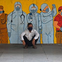 Un hombre que espera su tren se sienta frente a un mural sobre guerreros del coronavirus Covid-19 de primera línea de diversas profesiones en una terminal ferroviaria en Mumbai. | Foto:Indranil Mukherjee / AFP