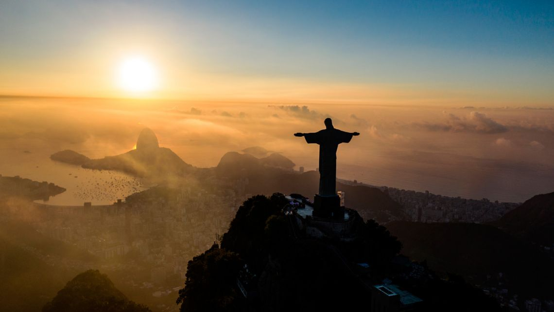 The sun rises in front of the Christ the Redeemer statue in Rio de Janeiro on March 24, 2021. Christ the Redeemer is celebrating its 90th anniversary in October 2021 and is receiving restoration work to ensure that it looks its best for the public and visiting tourists.