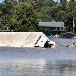 La gente rema junto a un contenedor rodeado por las inundaciones en una zona residencial del suburbio de Windsor en el noroeste de Sydney, después de que lluvias torrenciales azotaran el sureste de Australia durante días.   Foto:Saeed Khan / AFP