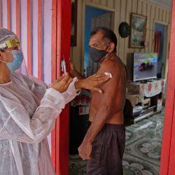 Joao Aquino Filho, es vacunado por un trabajador de la salud con una dosis de la vacuna COVID-19 Oxford-AstraZeneca en la comunidad de Nossa Senhora Livramento en las orillas del Río Negro cerca de Manaus, estado de Amazonas, Brasil.   Foto:Michael Dantas / AFP