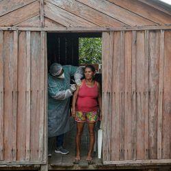 Un trabajador de salud del Departamento de Salud Indígena del Ministerio de Salud administra una segunda dosis de la vacuna COVID-19 a la paciente María Tereza en Sao José III do rio Maro, en la región de la Baja Amazonía del estado de Pará, cerca de Santarem en Brasil. | Foto:Tarso Sarraf / AFP