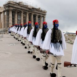 Miembros de la Guardia Presidencial caminan frente al templo del Partenón en la cima de la colina de la Acrópolis después de la ceremonia de izamiento de la bandera griega en Atenas. - Grecia celebra el bicentenario del inicio de la guerra de independencia del país contra el Imperio Otomano.   Foto:Petros Giannakouris / POOL / AFP