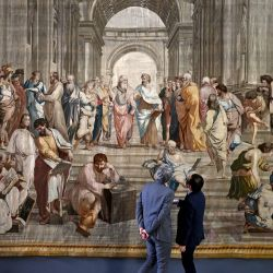Dos hombres miran un tapiz que representa  | Foto:Aris Messinis / AFP