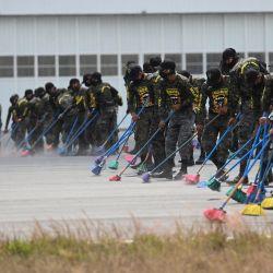 Miembros del Ejército de Guatemala barren cenizas de la pista del aeropuerto internacional La Aurora, luego de que las autoridades suspendieran sus operaciones por la caída de cenizas de la constante actividad eruptiva del volcán Pacaya, en la Ciudad de Guatemala.   Foto:Johan Ordonez / AFP