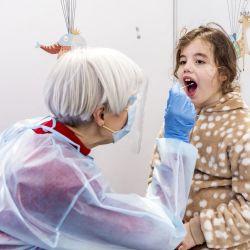 Un trabajador de salud toma una muestra de frotis de garganta de un niño para realizar una prueba del coronavirus Covid-19 en un centro especial de pruebas para niños en Ámsterdam. | Foto:Remko de Waal / ANP / AFP