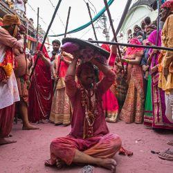 Mujeres hindúes golpean a un hombre con palos mientras celebran tradicionalmente el Lathmar Holi, el festival de colores de primavera cerca de un templo en la aldea de Barsana, en el estado de Uttar Pradesh, en India. | Foto:Xavier Galiana / AFP