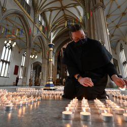 Un verger enciende una de las 4.161 velas que representan cada muerte de Covid-19 en el condado de Lancashire, luego de un servicio del decano de Blackburn, Peter Howell-Jones en la catedral de Blackburn, Blackburn, noroeste de Inglaterra, el primer aniversario de la primera bloqueo nacional del Covid-19.   Foto:Paul Ellis / AFP