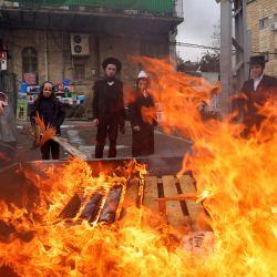 Hombres judíos ultraortodoxos queman artículos con levadura durante el ritual Biur Jametz en Jerusalén, antes de la festividad judía de Pesaj (Pascua judía). - Los judíos de todo el mundo celebran los ocho días de Pesaj (Pascua) para conmemorar el éxodo de los israelitas de la esclavitud en Egipto hace unos 3.500 años y su difícil situación al abstenerse de comer alimentos con levadura. | Foto:Emmanuel Dunand / AFP