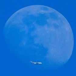 La silueta de un avión se ve frente a la luna en Moscú. | Foto:Yuri Kadobnov / AFP