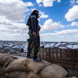 Un miembro de las fuerzas de seguridad internas kurdas observa cómo otro grupo de familias sirias es liberado del campamento de al-Hol, dirigido por los kurdos, que alberga a presuntos familiares de combatientes del grupo Estado Islámico, en la gobernación de Hasakeh, en el noreste de Siria. | Foto:Delil Souleiman / AFP