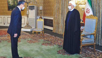 Solemne. El canciller chino Wang Yi con el presidente iraní Hassan Rohuani. Las dos delegaciones definieron ayer los últimos detalles y los dos cancilleres con el texto del acuerdo que deberá ser aprobado ahora por los respectivos parlamentos.