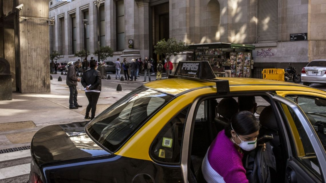 A passenger gets out of a taxi in Buenos Aires' financial district.